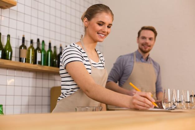Au travail. joyeuse jeune femme positive souriante et regardant ses notes tout en travaillant dans le café
