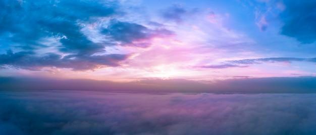 A l'aube au-dessus des nuages, la lumière du soleil violette illumine le ciel du matin.