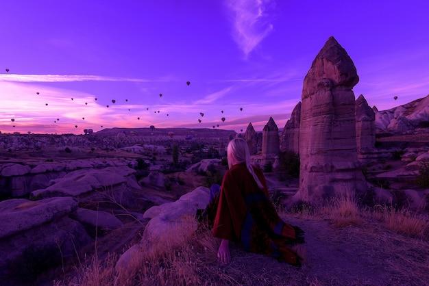 Aube magique à göreme cappadoce turquie. une fille dans un canyon en vêtements traditionnels entourée de ballons dans les rayons du soleil levant