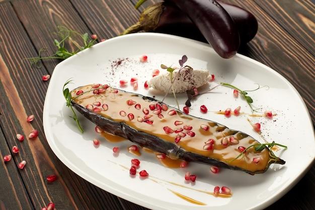 Aubergine au four avec du fromage et des graines de grenade, sur une plaque blanche, sur table en bois