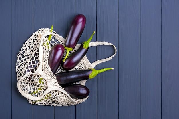 Aubergine dans un sac en maille écologique avec aubergine sur bois gris foncé.