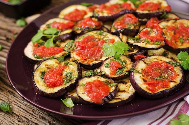 Aubergine grillée avec sauce tomate, ail, coriandre et menthe. nourriture végétalienne. aubergine grillée.