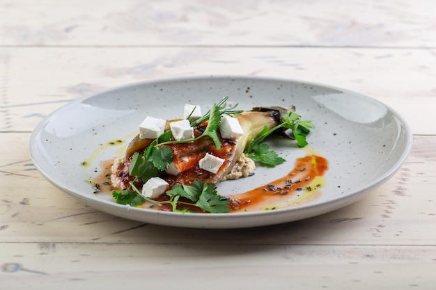 Aubergines au four juteuses et appétissantes avec des tomates et des herbes sur une assiette blanche servie dans un restaurant.
