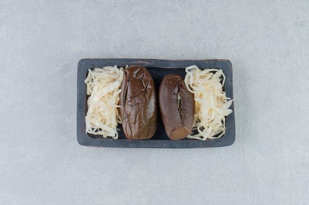 Aubergines et choucroute fermentées sur plaque noire.