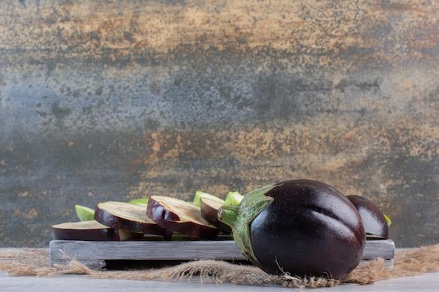 Aubergines et courgettes tranchées sur planche de bois. photo de haute qualité