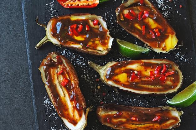 Aubergines cuites au four avec sauce au citron vert sur une planche en pierre.