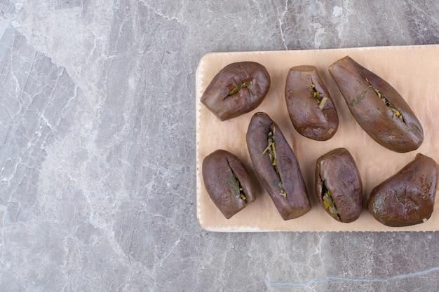 Aubergines farcies marinées sur planche de bois.