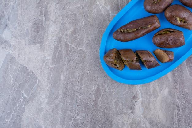 Aubergines farcies marinées sur plaque bleue.