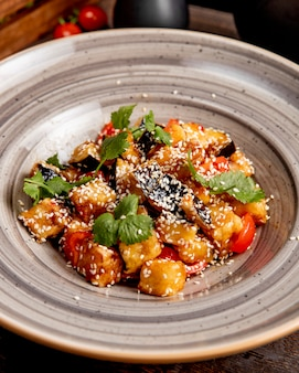 Aubergines frites aux tomates préparées en sauce et servies avec coriandre