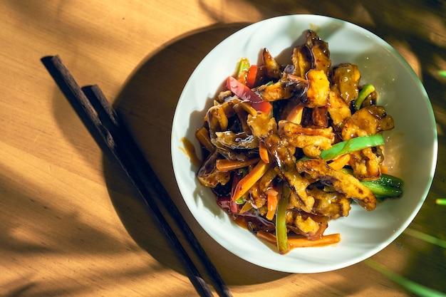 Aubergines frites en sauce aigre-douce avec poivrons et tomates. recette et cuisine chinoise