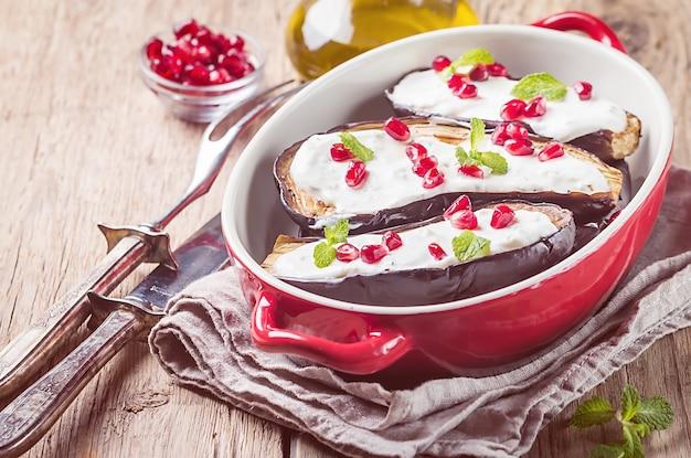 Aubergines grillées avec sauce au yogourt à l'ail et grenade sous forme rouge pour la cuisson sur bois