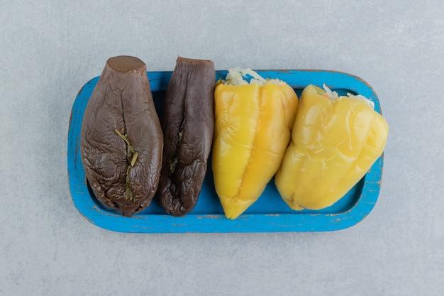 Aubergines et poivrons de cornichons délicieux sur la plaque en bois