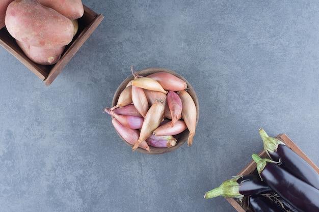 Aubergines, pommes de terre et oignons dans des caisses en bois.
