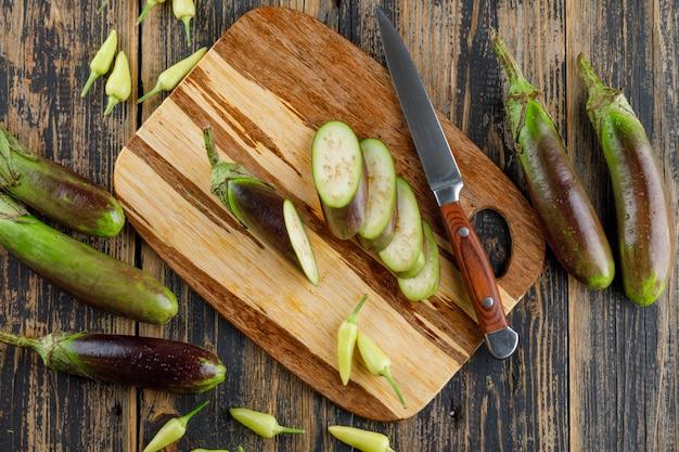 Aubergines avec des tranches, un couteau, des poivrons sur une planche à découper en bois, à plat.
