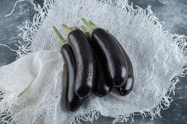 Aubergines violettes bio fraîches sur sac.