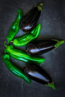 Aubergines violettes mûres fraîches vert composition de poivrons italiens sur fond sombre, une alimentation saine