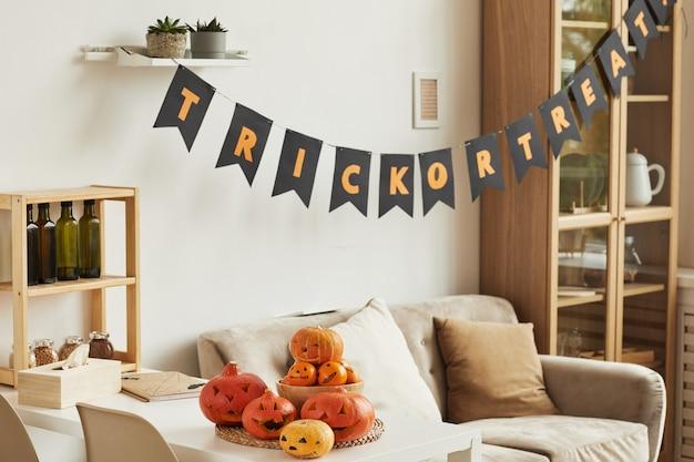 Aucun peuple horizontal tourné de l'intérieur de la chambre moderne avec guirlande de lettrage trick or treat et citrouilles sculptées préparées pour la fête d'halloween