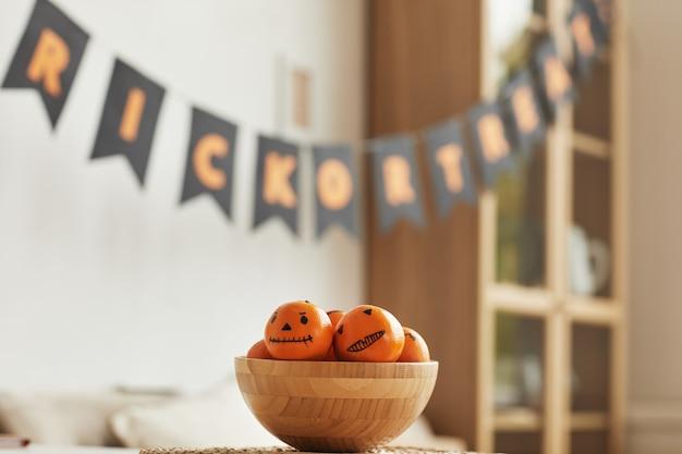 Aucun peuple horizontal tourné de mandarines fraîches avec jack o 'lantern visages dessinés sur eux couché dans un bol en bois pour la fête d'halloween