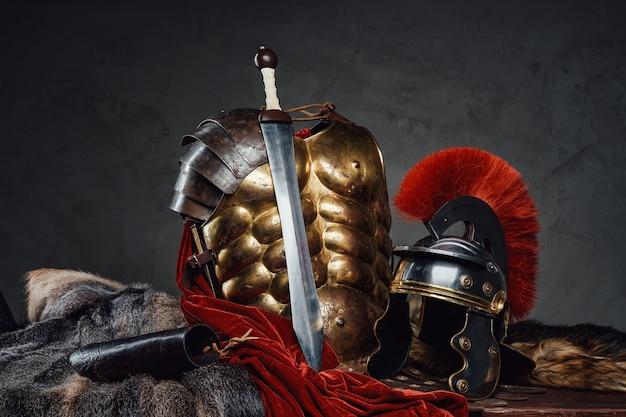 Aucun peuple tourné en studio d'une armure de bronze antique et d'un casque avec gladius sur fond sombre.