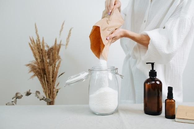 Aucune image de tête d'une chimiste préparant un mélange pour des cosmétiques respectueux de l'environnement sur une table. verser la poudre blanche dans un bocal.