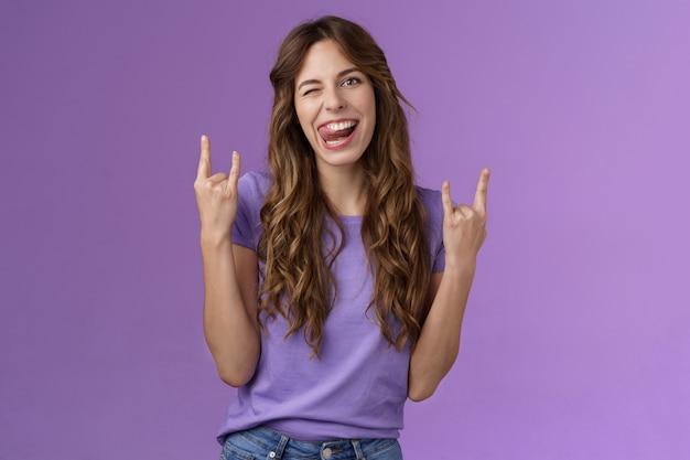 Audacieuse femme séduisante drôle et amusante s'amuser profiter d'une fête géniale organiser un concert de musique rassemblement spectacle rock-n-roll signe de métaux lourds joyeuse langue de bâton clin d'œil effronté fond violet. mode de vie.