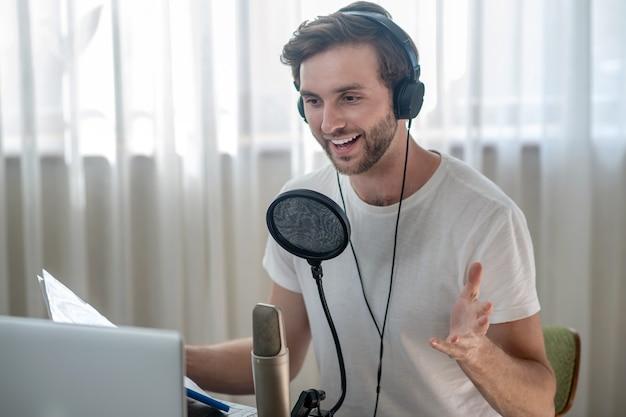 Audioconférence. jeune homme barbu assis dans des écouteurs et ayant une conférence audio