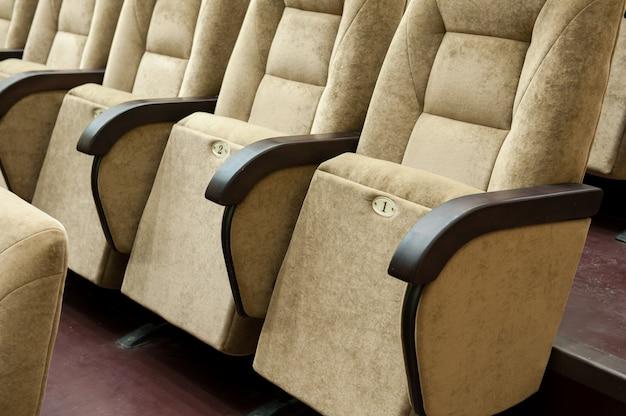 Un auditorium vide avec des chaises beiges, un théâtre ou une salle de conférence