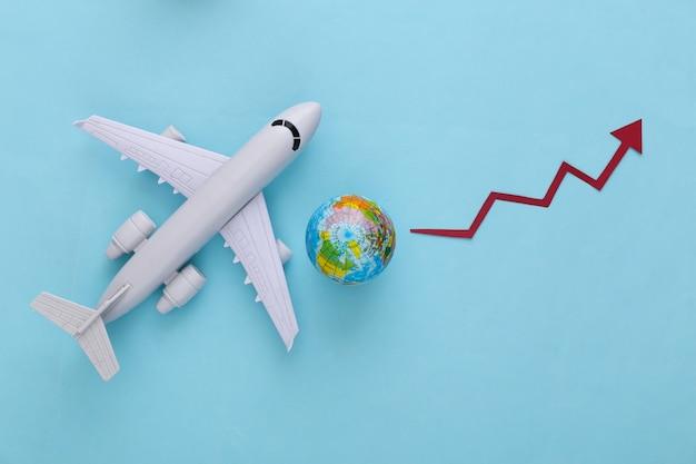 L'augmentation des voyages en avion. avion avec globe, la flèche de croissance a tendance à monter sur un bleu