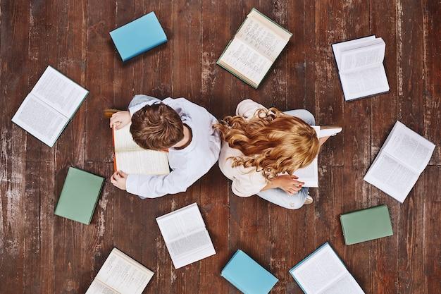 Aujourd'hui un lecteur demain un leader enfants assis près des livres en lisant ils tiennent des livres