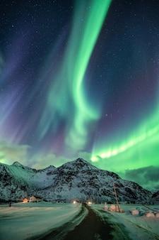 Aurora borealis, explosion d'aurores boréales sur la montagne enneigée et la route en hiver à flakstad, îles lofoten, norvège