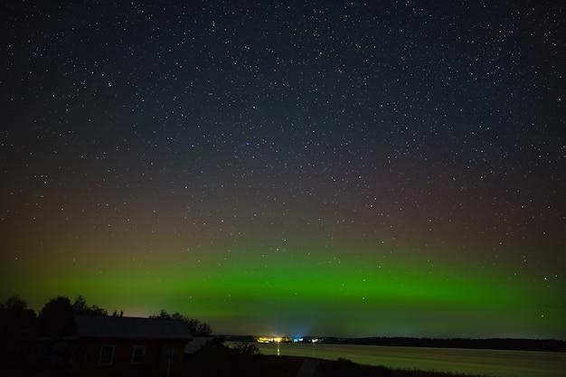 Aurore boréale au-dessus de la ville sur la côte. lumières polaires dans le ciel étoilé de la nuit au-dessus du lac.