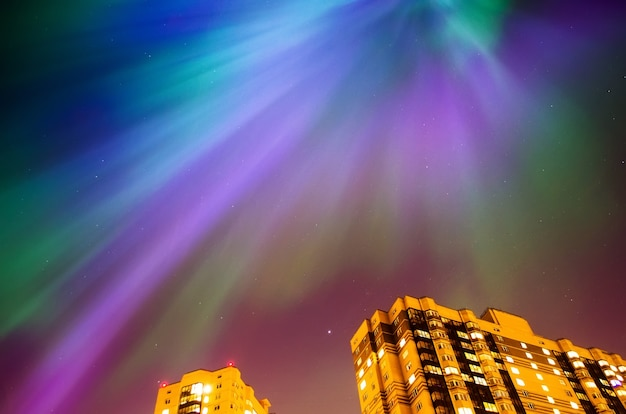 Aurore boréale nuit étoilée sur la ville et les maisons.