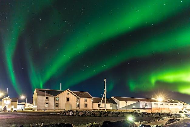 Aurores boréales colorées (aurora borealis) avec un entrepôt au premier plan en islande