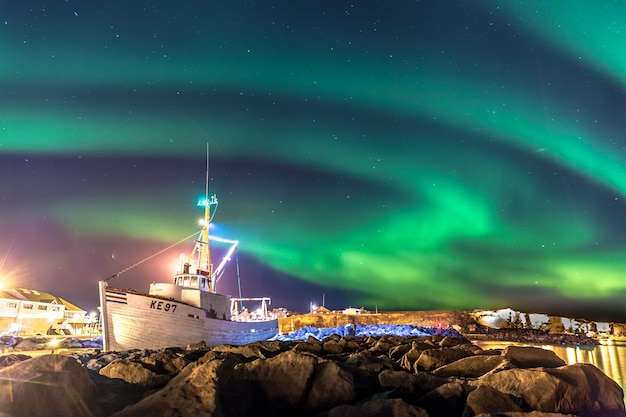 Aurores boréales colorées avec un bateau au premier plan en islande