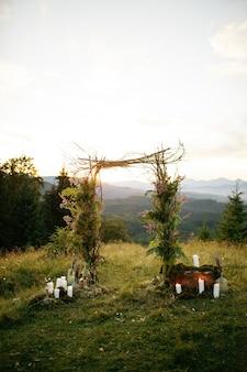 Autel de mariage fait de branches vertes et de bâtons en bois