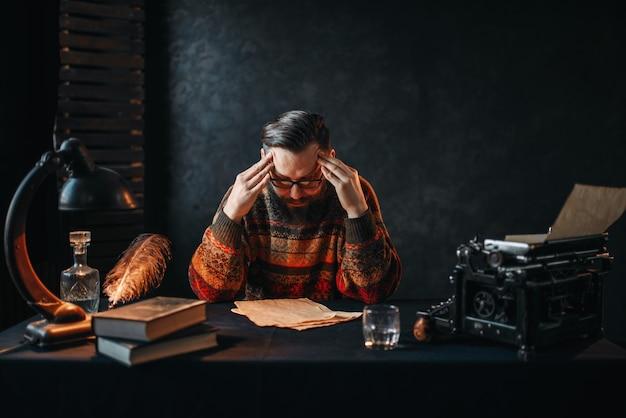 Auteur barbu dans des verres lisant son travail