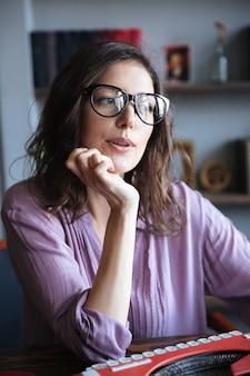 Auteure mûre pensive dans les lunettes en pensant et en regardant ailleurs