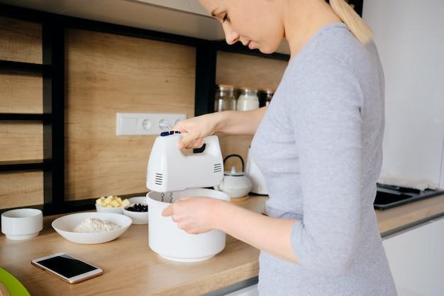 Authentique femme à l'aide d'un mélangeur à main