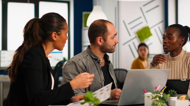 Authentique groupe diversifié d'hommes d'affaires enthousiastes, de professionnels du marketing, utilisant un ordinateur portable, discutant lors d'une réunion d'idées de projet, remue-méninges sur la stratégie d'entreprise de démarrage assis à offi