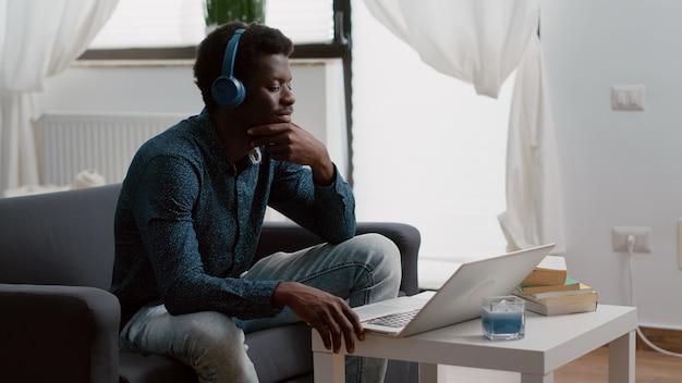 Authentique homme afro-américain souriant utilisant un ordinateur portable avec des écouteurs, travaillant à domicile ou en écoutant un webinaire ou des cours en ligne en indépendant. prendre un webinaire sur internet depuis le bureau à domicile