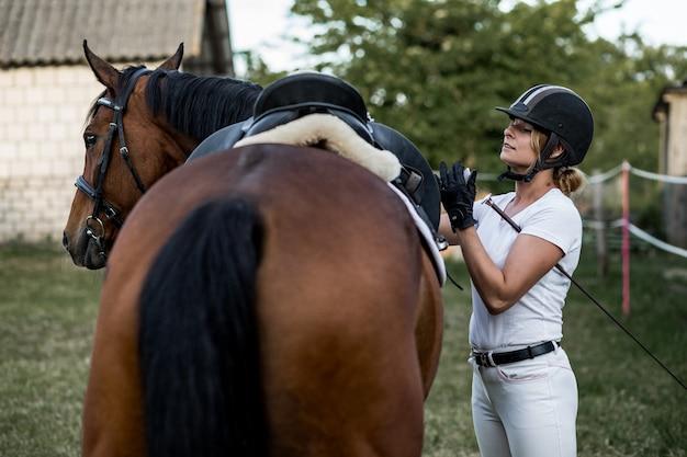 Autiful femme vêtue de vêtements de sport se prépare pour une séance d'entraînement à cheval. soirée d'été.