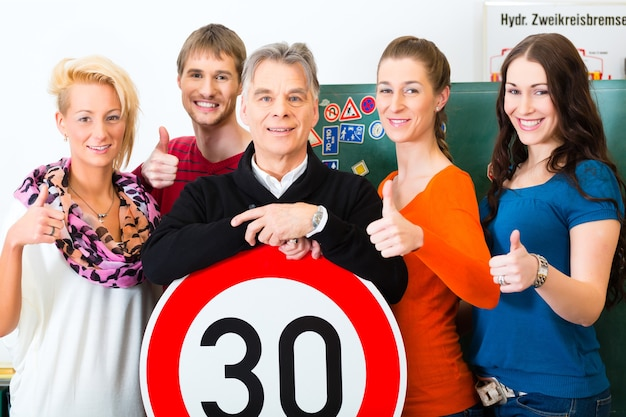 Auto-école - moniteur de conduite et élèves conducteurs regardent un panneau routier tempo trente