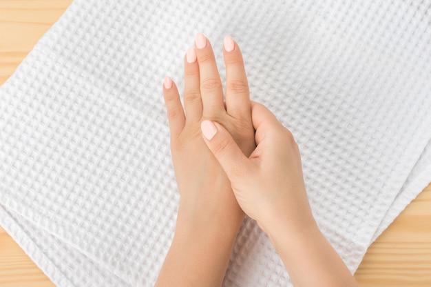 Auto-massage des mains par une jeune femme caucasienne. santé des doigts et des articulations des mains. auto-massage. massage sain. gros plan main de personne masser sa main de la douleur dans un concept sain