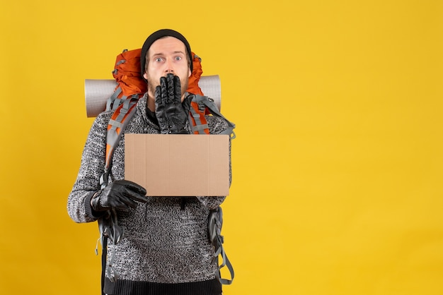 Auto-stoppeur mâle choqué avec des gants en cuir et un sac à dos tenant un carton vierge