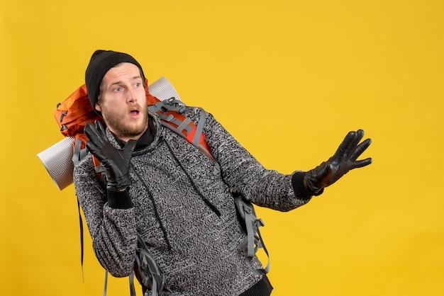 Auto-stoppeur mâle effrayé avec des gants en cuir et un sac à dos restant à l'écart de quelque chose