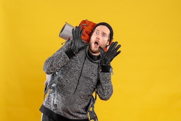 Auto-stoppeur mâle effrayé avec des gants en cuir et un sac à dos