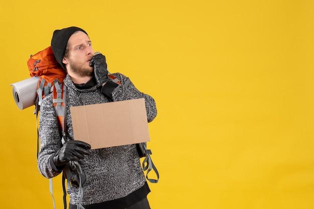 Auto-stoppeur mâle inquiet avec des gants en cuir et un sac à dos tenant un carton vierge