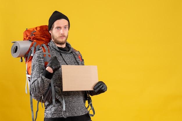 Auto-stoppeur mâle avec sac à dos tenant un carton vierge