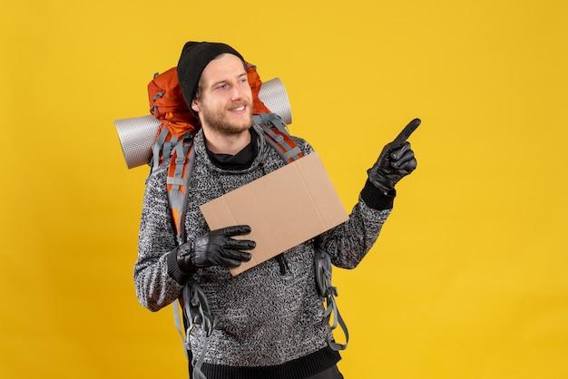 Auto-stoppeur mâle souriant avec sac à dos tenant un carton vierge