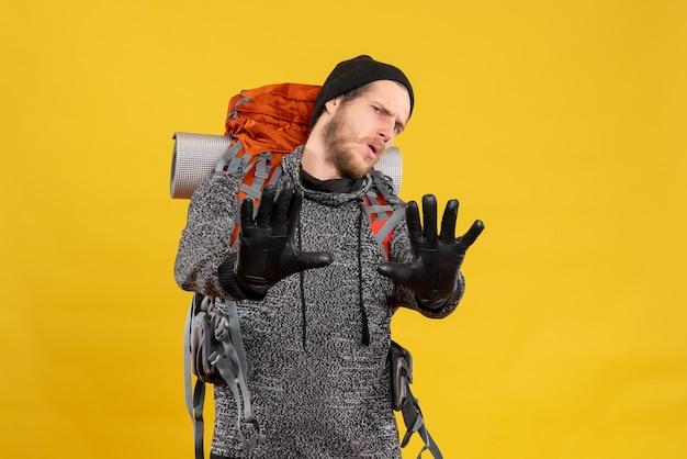 Auto-stoppeur masculin avec des gants en cuir et un sac à dos faisant un panneau d'arrêt